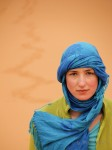 Girl in blue walking across the Northern Sahara.