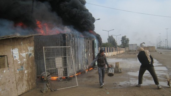People try to extinguish flames at a gas station after clashes between Iraqi army soldiers and Sunni gunmen in Fallujah, 65 kilometers (40 miles) west of Baghdad, Iraq, Tuesday, Dec. 31, 2013. (AP Photo)