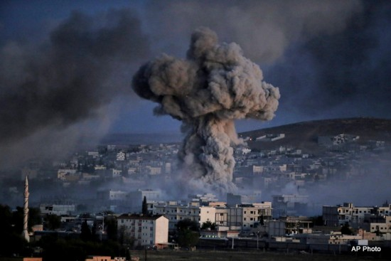 Thick smoke from an airstrike by the US-led coalition rise in Kobani, Syria, as seen from a hilltop on the outskirts of Suruc, at the Turkey-Syria border, Monday, Oct. 20, 2014 .  Photo by Lefteris Pitarakis/AP