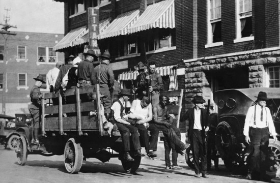 "In the spring of 1921, a white mob leveled ""Black Wall Street"" in Tulsa, Oklahoma. Here, wounded prisoners ride in an Army truck during the martial law imposed by the Oklahoma governor in response to the race riot. (Hulton-Deutsch Collection/Corbis)"